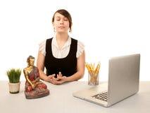 Frau, die an ihrem Schreibtisch meditiert Stockbild