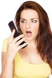 Frau, die ihrem Telefon entsetzt betrachtet Lizenzfreies Stockfoto