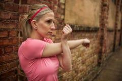 Frau, die ihren Arm ausdehnt Stockfotos