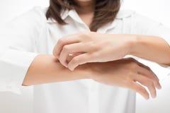 Frau, die ihren Arm verkratzt stockbild