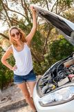 Frau, die ihren Automotor nach einem Zusammenbruch kontrolliert Lizenzfreie Stockbilder