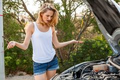Frau, die ihren Automotor nach einem Zusammenbruch kontrolliert Lizenzfreies Stockfoto
