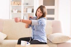 Frau, die ihren Blutdruck überprüft Lizenzfreies Stockbild