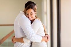 Frau, die ihren Ehemann umarmt stockfotografie
