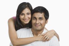 Frau, die ihren Ehemann von hinten umarmt stockfotografie