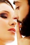 Frau, die ihren Finger auf die Lippen des Mannes setzt Lizenzfreies Stockfoto