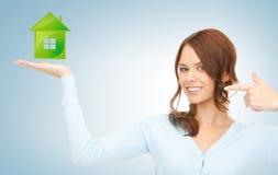 Frau, die ihren Finger auf grünes Öko-Haus zeigt Stockfotos