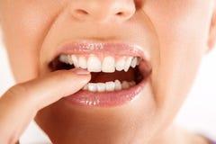 Frau, die ihren Finger mit den Zähnen beißt lizenzfreies stockbild