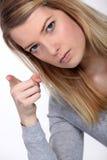 Frau, die ihren Finger rüttelt Stockbild