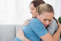 Frau, die ihren Freund in ihren Armen nimmt Stockfoto