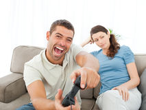Frau, die ihren Freund spielt Videospiel wartet Lizenzfreie Stockbilder