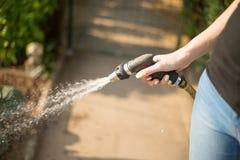 Frau, die ihren Garten gießt Stockfotos