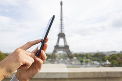 Frau, die ihren Handy vor Eiffelturm verwendet Stockbild