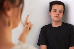 Frau, die ihren Jugendlichsohn konferiert, der mit gebohrte expres hört stockbild