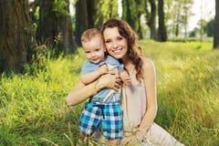Frau, die ihren kleinen Sohn umarmt Stockbilder