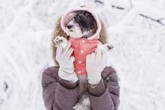 Frau, die ihren kleinen weißen Hund im Winterwald umarmt schneiende Zeit Lizenzfreie Stockbilder