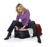 Frau, die ihren Koffer schließt Lizenzfreies Stockbild