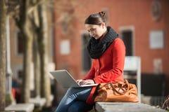 Frau, die ihren Laptop in der Straße verwendet lizenzfreie stockfotografie