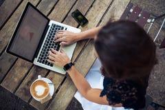Frau, die ihren Laptop an einer Kaffeestube verwendet Stockbild