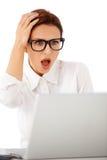 Frau, die ihren Laptop im Horror betrachtet Lizenzfreie Stockfotografie