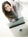 Frau, die ihren Laptop im Wohnzimmer verwendet. Stockfotografie