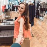 Frau, die ihren Mann schleppt, um das Einkaufen in der Butike oder im Speicher umzuarbeiten Lizenzfreie Stockfotografie