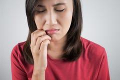 Frau, die ihren Mund verkratzt lizenzfreies stockfoto