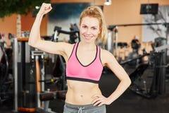 Frau, die ihren Muskel zeigt und ihre Faust cletching Stockbilder