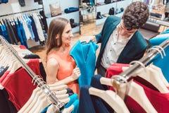 Frau, die ihren Partner von ein neues Kleiderst. in Mode kaufen überzeugt stockfotos