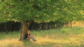 Frau, die ihren Smartphone in der Natur verwendet Stockfotografie