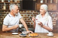 Frau, die ihren trinkenden Kaffee des Ehemanns betrachtet lizenzfreie stockbilder