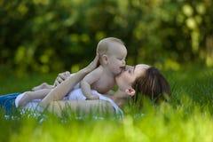 Frau, die im Arm ein Baby in einem Garten hält und auf dem Gras liegt Stockbild