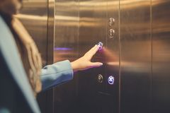 Frau, die im Aufzug steht und Knopf bedrängt stockbild
