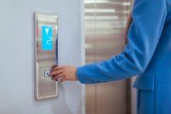 Frau, die im Aufzug steht und Knopf in Einkaufszentrum bedrängt stockfotos