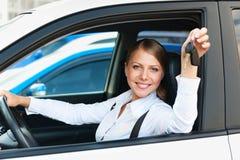 Frau, die im Auto sitzt und die Autotasten zeigt Stockbilder