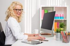 Frau, die im Büro auf stationärem Computer arbeitet Stockbilder