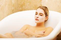 Frau, die im Bad mit Gesichtsmaske sich entspannt Lizenzfreie Stockfotos