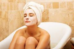 Frau, die im Bad mit Gesichtsmaske sitzt Lizenzfreie Stockfotos