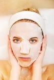 Frau, die im Bad mit Gesichtsmaske sitzt Stockbild