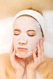 Frau, die im Bad mit Gesichtsmaske sitzt Lizenzfreie Stockbilder