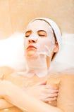 Frau, die im Bad mit Gesichtsmaske sitzt Lizenzfreie Stockfotografie