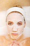 Frau, die im Bad mit Gesichtsmaske sitzt Lizenzfreies Stockbild