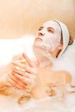 Frau, die im Bad mit Gesichtsmaske und Glas Champagner sitzt Stockfotos