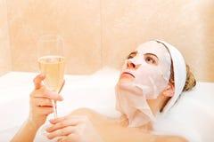 Frau, die im Bad mit Gesichtsmaske und Glas Champagner sitzt Lizenzfreies Stockbild