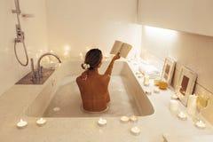 Frau, die im Bad mit Kerzen sich entspannt stockfoto
