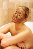 Frau, die im Bad mit SchokoladenGesichtsmaske sitzt Stockfotografie