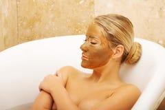 Frau, die im Bad mit Schokoladenmaske auf Gesicht sich entspannt Stockfotografie