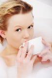 Frau, die im Bad, Trinkbecher Kaffee sich entspannt Lizenzfreie Stockfotos
