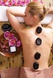 Frau, die im Badekurortsalon mit heißen Steinen auf Körper sich entspannt Stockbilder