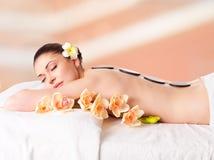 Frau, die im Badekurortsalon mit heißen Steinen sich entspannt Lizenzfreie Stockbilder